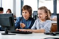 Boy pointing while using desktop pc with friend at cute little desk in school computer lab Stock Image
