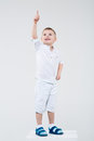 Boy points a finger somewhere in white clothes and slippers Royalty Free Stock Image