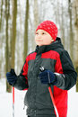 Boy with poles standing in winter forest and looking sideways Royalty Free Stock Photos