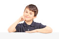 Boy posing behind blank panel on white background Stock Photos