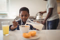 Boy pouring milk into breakfast cereals bowl in kitchen Royalty Free Stock Photo