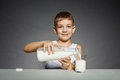Boy pouring milk into glass smiling Royalty Free Stock Images