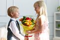 Boy is presented flowers to girl studio shot Royalty Free Stock Photos