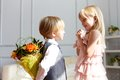 Boy is presented flowers to girl studio shot Stock Image