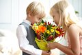 Boy is presented flowers to girl studio shot Royalty Free Stock Photography