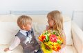 Boy is presented flowers to girl studio shot Royalty Free Stock Image