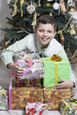 Boy is protecting christmas gifts young with many Stock Photo