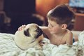 Boy and pug lying on a soft bed with her friend breed puppy Stock Images