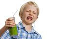 Boy pulling funny face holding green smoothie a young looking very disgusted a isolated on white Stock Image