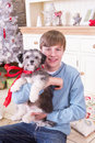 Boy with puppy at christmas holding a time he is looking the camera and smiling and the has a red bow around its neck Royalty Free Stock Photo