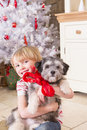 Boy with puppy at christmas little a time he is looking the camera and the has a red bow around its neck Stock Image