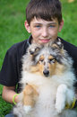 Boy with puppy teenager a collie harlequin close up portrait facial freckles the s blue eyes dressed in a black shirt Stock Image
