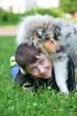 Boy with puppy teenager a collie harlequin lying on green grass lying on top of the on the face of a teenager Stock Photography