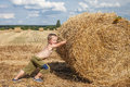 Boy pushes bale of straw young in the field Royalty Free Stock Photo