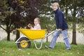 Boy pushing girl in wheelbarrow Royalty Free Stock Photo
