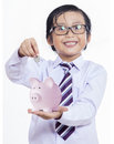 Boy puts the coin into a piggy bank happy isolated on white Royalty Free Stock Photography