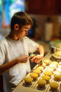 Boy putting icing on cupcakes a young year old Stock Photos