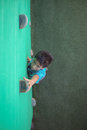 Boy reaching climbing holds on green wall Royalty Free Stock Photo