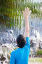 Boy reaching up to feel water in a waterfall Royalty Free Stock Photo