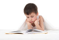 Boy read a book in bed isolated Royalty Free Stock Photos