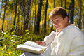 Boy reading book in forest Royalty Free Stock Photos
