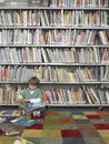 Boy reading book in library full length of young Royalty Free Stock Images