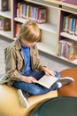 Boy reading book in school library full length of young Stock Photos
