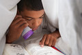 Boy reading book with torch under duvet at night Royalty Free Stock Photography