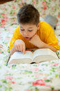 Boy reads a book in bed Royalty Free Stock Photo
