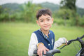 A boy is ready to get on a bike to explore the natural land in blue and white top black green Stock Images