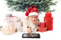 The boy in red cap points into tablet pc monitor against fir tree Stock Photos