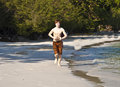 Boy with red hair in bathing cloths young running at the beautiful beach Stock Photography
