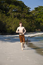 Boy with red hair in bathing cloths young running at the beautiful beach Stock Photos
