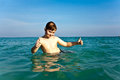 Boy with red hair is enjoying the clear warm water at the beautiful beach Stock Photography