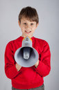 Boy in red pullover holding loudspeaker on bright background