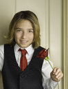 Boy with red rose valentine s day a long brown hair and brown eyes dressed in a vest from a tuxedo white shirt and tie smiles and Stock Photos