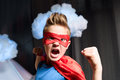 Boy in red superhero costume with fighting gesture screaming