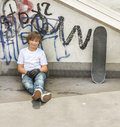 Boy relaxes with his skate board at the skate park Royalty Free Stock Photo
