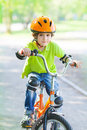 The boy rides a cycle on bicycle trail in city park Stock Photos
