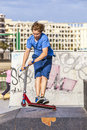Boy rides his scooter at the skate park Stock Image
