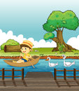 A boy riding on a boat followed by ducks illustration of Royalty Free Stock Photos