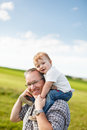 Boy riding his father s shoulders in a field Royalty Free Stock Photo