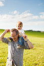 Boy riding his father s shoulders in a field Stock Images