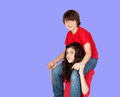 Boy riding on his sister a blue background Royalty Free Stock Image