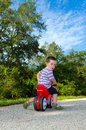 Boy riding on a toy motorbike Stock Images