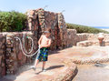 Boy rinsing off sea sand at an outdoor shower little using a hosepipe to spray his feet and summer shoes a tropical seaside Royalty Free Stock Image