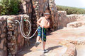 Boy rinsing off sea sand at an outdoor shower little using a hosepipe to spray his feet and summer shoes a tropical seaside Stock Images