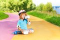 Boy rollerblading and drink water from bottle happy thee years old sit with in the park on sunny summer day Stock Photography