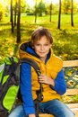 Boy with rucksack portrait of happy years old sitting on the bench backpack after school Stock Photo