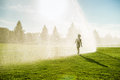 Boy running around the golf courses which are watered with fountains little Stock Photos